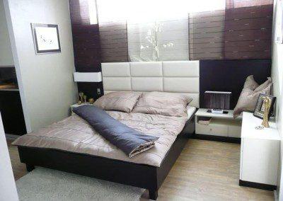 Doppelbett mit Lederpaneel im Kopfbereich.
