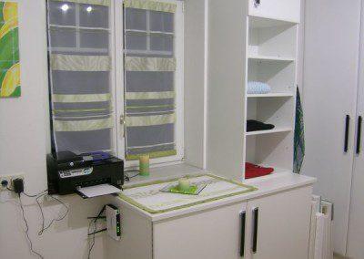 Begehbarer Schrankraum der bequem Platz für Staubsauger und integriertes ausziehbares Bügelbrett bietet.