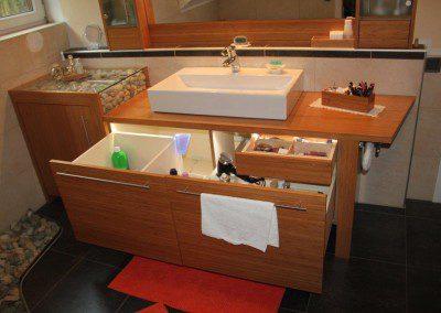 Badezimmer Einrichtung in Bambus Caramel mit Ordnungssystem in den Auszugsladen und indirekter Beleuchtung.