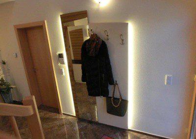 Gästegarderobe weiß lackiert, in Kombination mit Zebrano Wandpaneel mit Spiegel und indirekter Wandbeleuchtung.