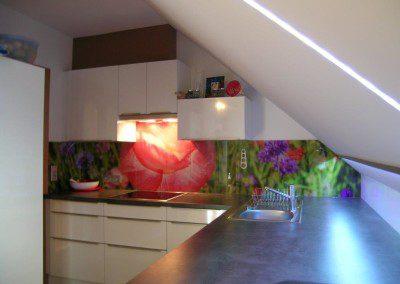 Einbauküche unter Dachschräge. Glaswandschoner mit Blumenmotiv.