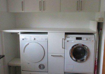 Waschküchenverbau mit eingebautem Trockner und Waschmaschine.