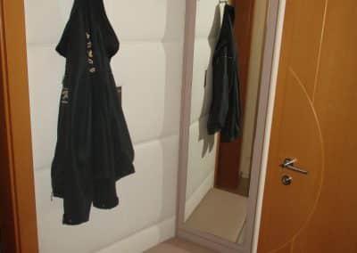 Gästegarderobe mit Lederwand und freischwebender Sitzgelegenheit. Spiegelpaneel zum öffnen.
