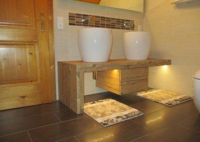 Badezimmermöbel mit aufgesetzten Waschbecken und zwei darunterliegenden Laden.