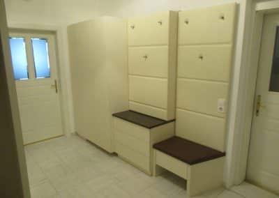 Creme farbenes Vorzimmer mit matter Oberfläche. Grifflose Ausführung mit TIP ON. E-Kasten und Garderobenwand mit abgenähter Leder Tapezierung.