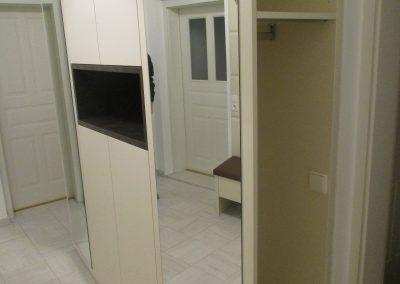 Creme farbenes Vorzimmer mit matter Oberfläche. Grifflose Ausführung mit TIP ON. Zwei offene Garderobenschränke mit Spiegelwand.